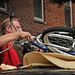 A dad wrestles his son's bike from the roof of the family SUV.