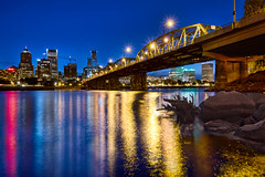 Dancing Lights on the Willamette River at Blue Hour - HDR (David Gn Photography) Tags: sunset reflection tree skyline night oregon buildings portland lights star evening log rocks downtown cityscape waterfront dancing hawthornebridge bluehour jam willametteriver hdr eastbankesplanade bursts 3xp canoneos7d sigma1020mmf35exdchsm sigma50th