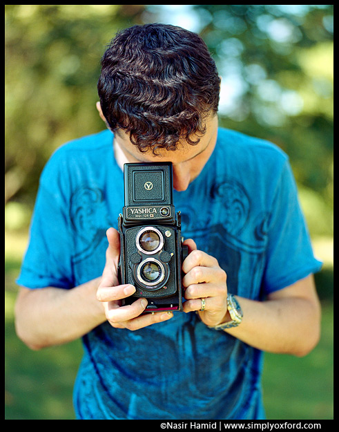 A photographer holding a Yashica twin lens reflex camera