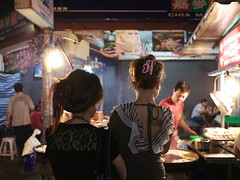 Waiting in line (weizor) Tags: portrait people food tattoo night lumix lights women asia shadows taiwan panasonic nightmarket chiayi streetfood jiayi tw micro43 microfourthirds 20mmf17asph dmcg3