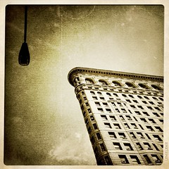 Reaching Out (street level) Tags: nyc newyorkcity travel urban building art sepia architecture skyscraper manhattan officebuilding landmark lamppost gothamist flatiron iphone historicsite arethesebuildings
