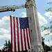 The US Flag is raised from a ladder truck before the start of the ceremony.