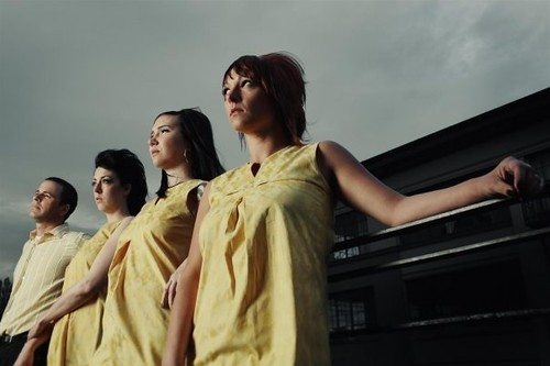 Three women and a man dressed in yellow lean against a car and stare off into the sky.
