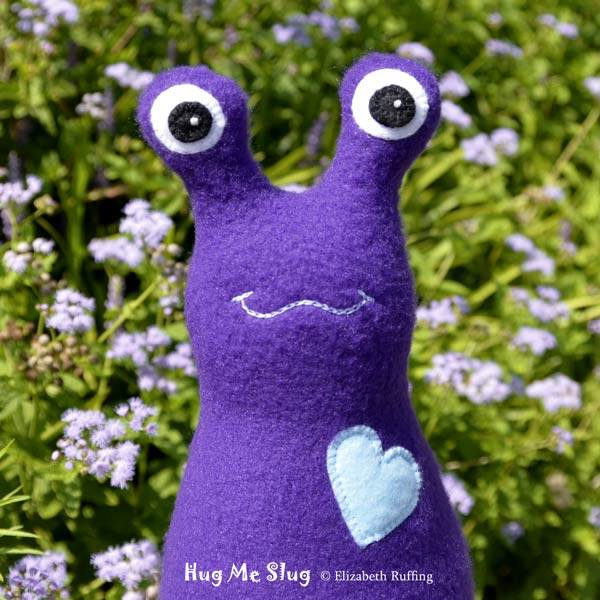 Dark purple fleece Hug Me Slug by Elizabeth Ruffing, with purple ageratum