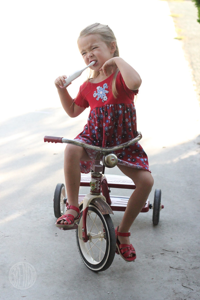 young child brushing her teeth while riding a tricycle