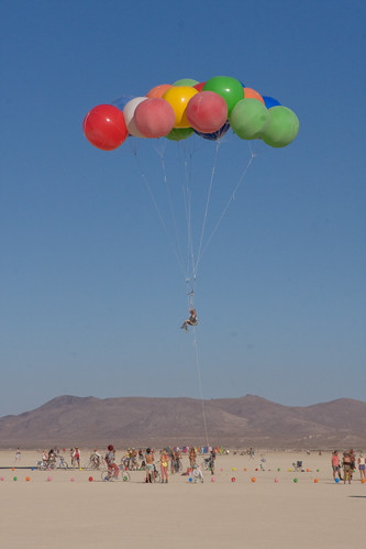 Photo of a man held aloft over the playa by a bunch of huge, colourful balloons.