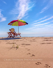Stay Awhile (Craig - S) Tags: park wood travel blue shadow summer vacation sky usa cloud dog sun white lake holiday beach water grass hat clouds america umbrella table relax photography reading coast us photo wooden sand chair solitude day peace unitedstates state image photos michigan sandy dune shoreline relaxing tracks vivid books lakemichigan greatlakes prints grasses doggy but resting grains bathing canopy tanning colorsplash tranquil ludington sunhat beachchair masoncounty dogprints ludingtonmi couldbeanywhere