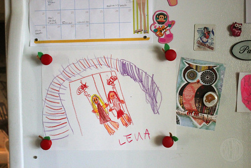 kids' art being displayed on refrigerator with apple magnets