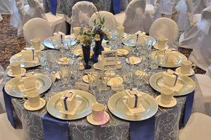 Table setting for a wedding white embroidered overlay and blue satin