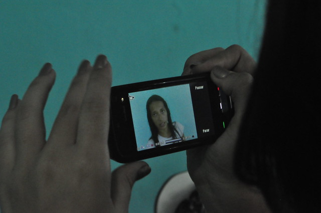 Photograph of a woman watching a video on a smart phone