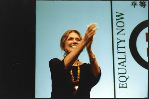 Steinem at a convention; she is standing on stage and clasping her hands