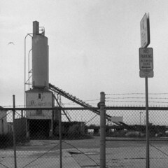 a bird, some machinery, a fence, a sign. (brian hefele) Tags: industrial hc110 delta things 124g stuff 3200 ilford doodads yashicamat geegaws d3200