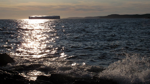 Iceberg, wave and sun shining on the water in Goose Cove