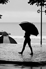 Walking in the rain... (Pablin79) Tags: trip sea summer people bw white black beach girl monochrome silhouette brasil digital umbrella canon eos reflex sand holidays 5d vacations pipa balneariocamboriu markii 70200mm shor 2011 canonef70200mmf4lisusm canoneos5dmarkii 5dmkii pabloreinsch pabloreinschphotography pablin79