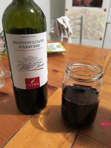 A bottle of red wine next to a small mason jar filled with wine.