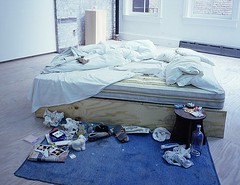 a bed in the middle of a room with stuff strewn around the edges