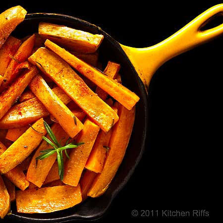 Roast sweet potatoes in yellow enamel skillet overhead view, black background