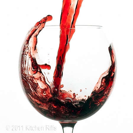 Pouring red wine into glass, wine curling above glass rim