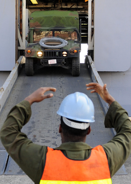 A Marine assigned to the 31st MEU directs a high mobility multipurpose wheeled vehicle out of the upper vehicle storage area