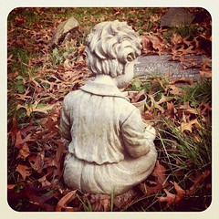 Little Stone Boy (back) (liquidnight) Tags: instagramapp square squareformat iphoneography uploaded:by=instagram foursquare:venue=4a9b11a1f964a5204a3420e3 iphone iphone4 instagram camera portland pdx lonefir cemetery graveyard stone statue memorial statuary boy child children mortality death small fragile young tender gentle sweet melancholy sitting seated fall autumn leaves foliage ground grass love affection grave mementomori back behind