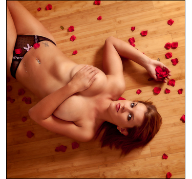 Woman poses for sensuous boudoir glamour nude photography on studio floor surrounded by rose petals.