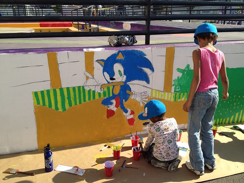 The kids from Youth UpRising help paing the mural