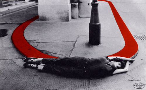 black and white photograph of a woman lying on the ground next to a red half-circle