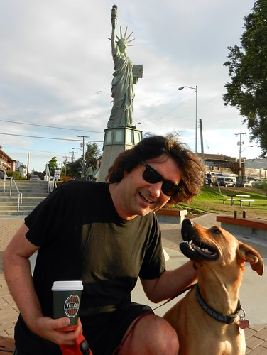 Behind sunglasses, Nick Boseck with a cuppa Tully's joe, Rosie the dog, under the Statue of Liberty at Alki Beach, West Seattle, Washington, USA by Wonderlane
