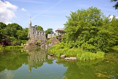 Belvedere Castle in Central Park (jiuguangw) Tags: park newyorkcity trees sky lake newyork reflection castle nature water grass architecture clouds rocks day stones centralpark flag belvederecastle pwpartlycloudy