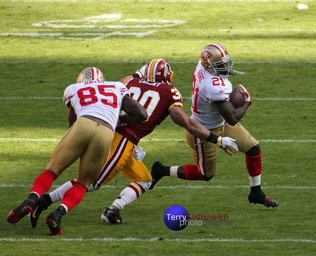 LaRon Landry pursues RB FRANK GORE, while Vernon Davis blocks.