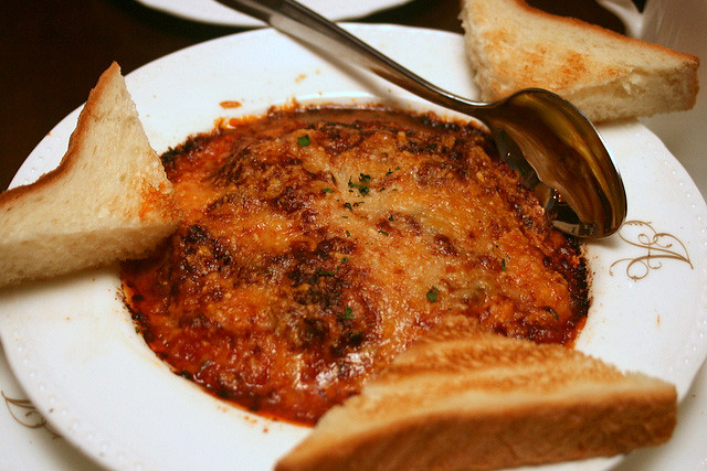 Scrambled egg gratin with tomato fondue, Paris ham, sauteed mushrooms and parmesan cheese, served with pain de mie toast