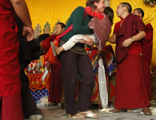Happy woman carrying a child after getting the long life blessing, running though the line, senior monks keep it moving, Tharlam Monastery of Tibetan Buddhism, Lamdre, Boudha, Kathmandu, Nepal by Wonderlane