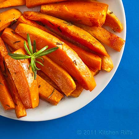 Roast sweet potatoes with rosemary garnish on white plate, blue background, overhead view