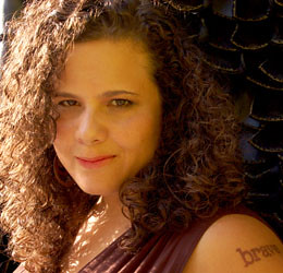 "Photo of Jaclyn Friedman from the shoulders up. Jaclyn is a white woman with very curly brown hair and a tattoo on her left shoulder that says ""brave."" She is smiling slightly."
