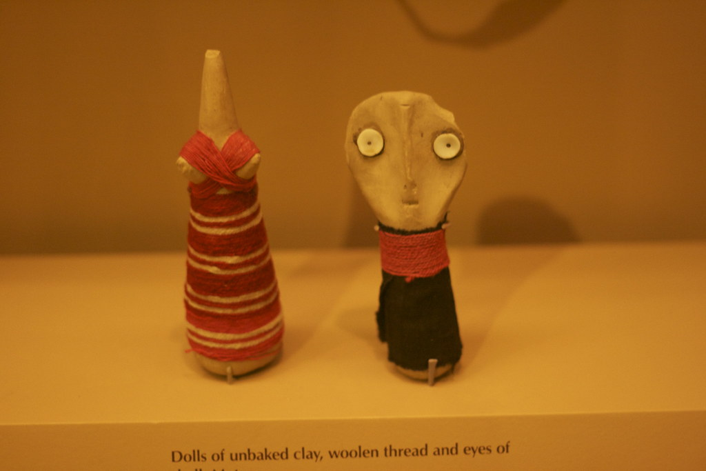 dolls of unbaked clay, woolen thread and eyes of shell Mataco.