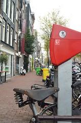 Primary Colours (Michaelasixfive) Tags: street windows tree amsterdam bike bicycle shop table spring post pavement seat bricks wheels bin