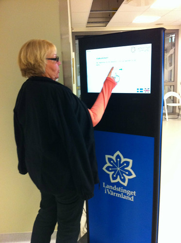Birgitta demonstrerar hur man anmäler seg på mammografiscreeningen