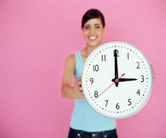 Prepare your voice prompts, message on hold system, and IVR for Daylight Savings Time - woman with clock