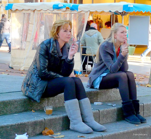 Girls sitting with coffee and cigarette .