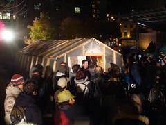 Photo: la foule et les médias regardant le SPCI inspecter la cuisine du campement, qui est un bâtiment dont les murs sont en toile
