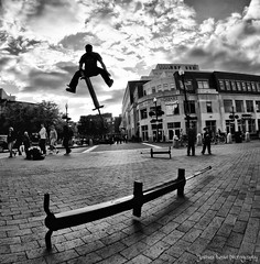 Pogo ( Mr. Dean ) Tags: street cambridge bw white black boston canon ma jump noir performance fisheye 7d harvardsquare stick spectators performer 8mm blanc pogo stunt rokinon