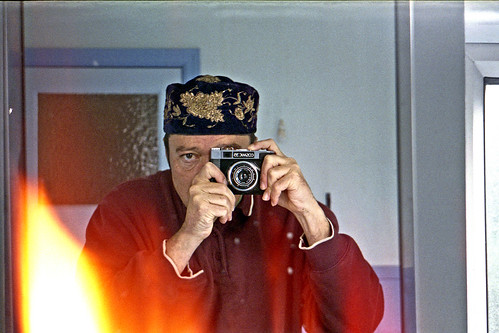 reflected self-portrait with Cosmic 35 camera and embroidered hat by pho-Tony
