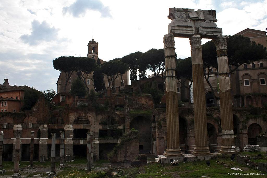 Au premier plan, les trois colonnes restantes du Temple des Dioscures, Castor et Pollux, et les ruines du Forum de César. Dominant le forum, on reconnaît la Mairie de Rome, sur le Capitole.