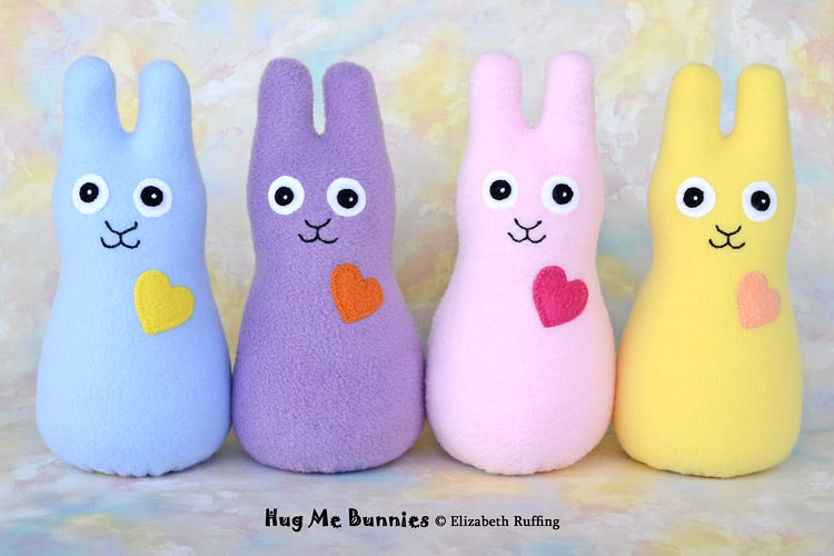 Assorted colors of fleece Hug Me Bunnies by Elizabeth Ruffing, in light blue, lavender, light pink, and daffodil yellow