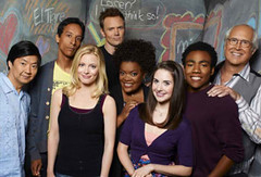 A photograph of the cast of Community, smiling in front of a blackboard