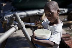 Haitian Child Collects Water in Camp for Displaced (United Nations Photo) Tags: boy camp portrait water haiti bucket child pipes photojournalism pump unitednations faucet bladder displaced idp portauprince unitednationsphoto