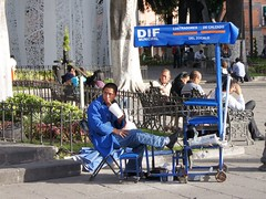 Shoe Shine Boy (StartTheDay) Tags: street city travel blue urban holiday man color colour male guy shirt catchycolors mexico shoe colorful bright drink candid photograph safe colourful amateur shoeshine hombre municipal zocalo homme mec 2011