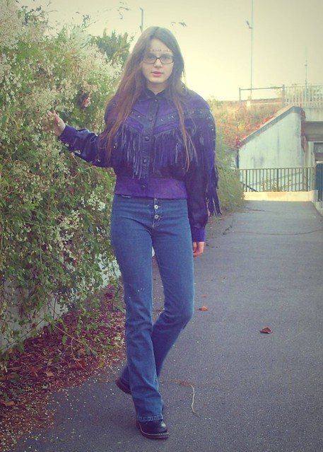 Purple fringed leather jacket, high-waisted blue jeans, colorful necklace as headband.