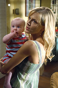 Rita from Dexter, a white woman with blond hair, holding a baby