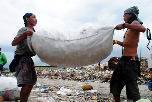 Two young scavengers carry a sackload of recyclables from the Inayawan landfill.